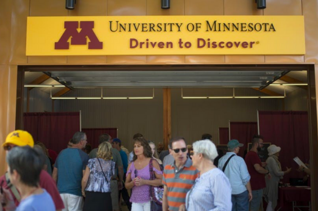 Building with yellow sign with University of Minnesota Logo and taglinef / People in and out the building